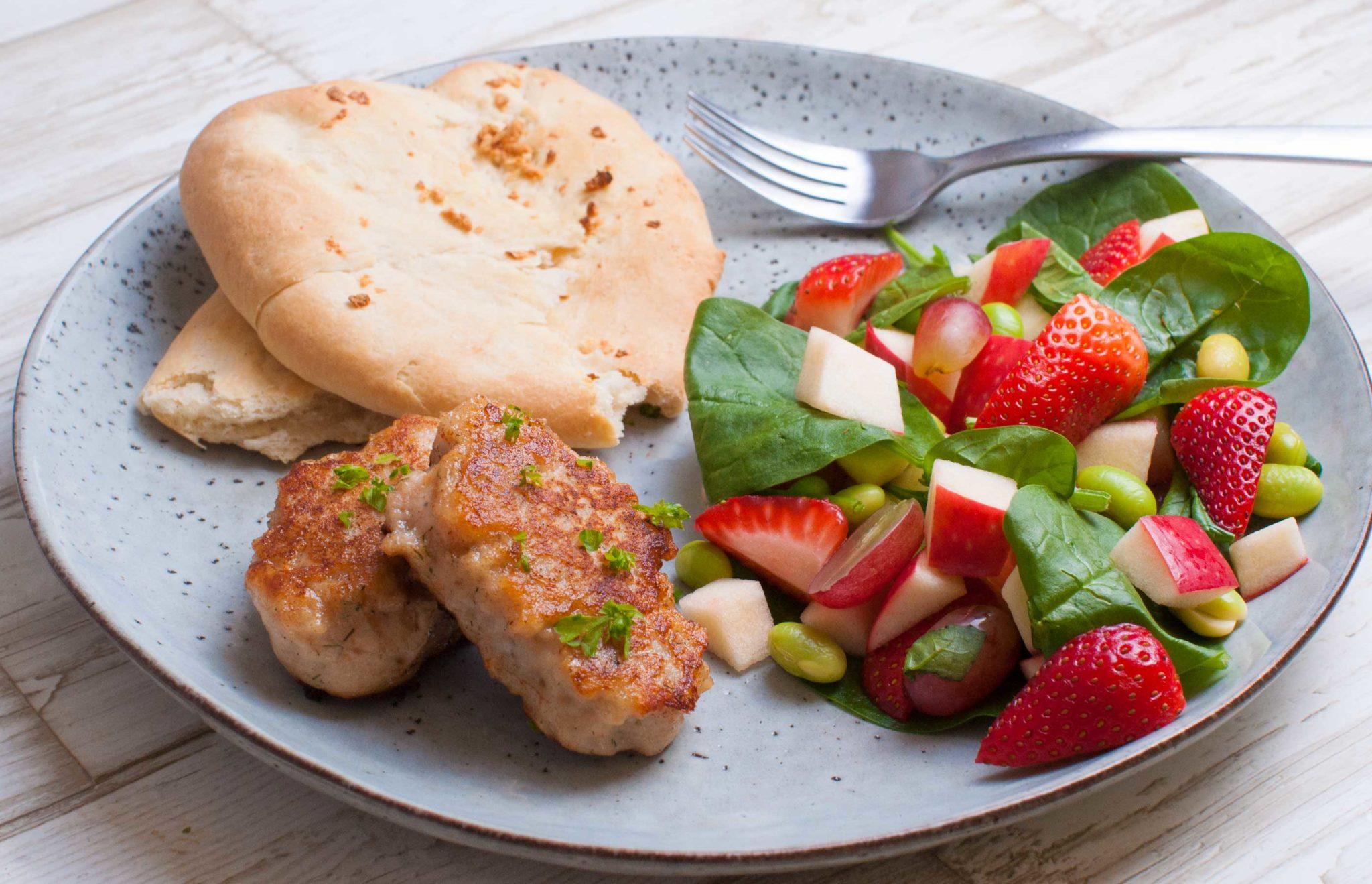 Fiskefrikadeller serveret med naanbrød og salat med jordbær og edamame